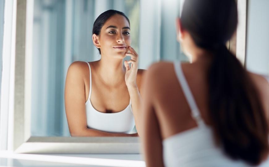 Ragazza di fronte allo specchio che controlla la pelle del viso
