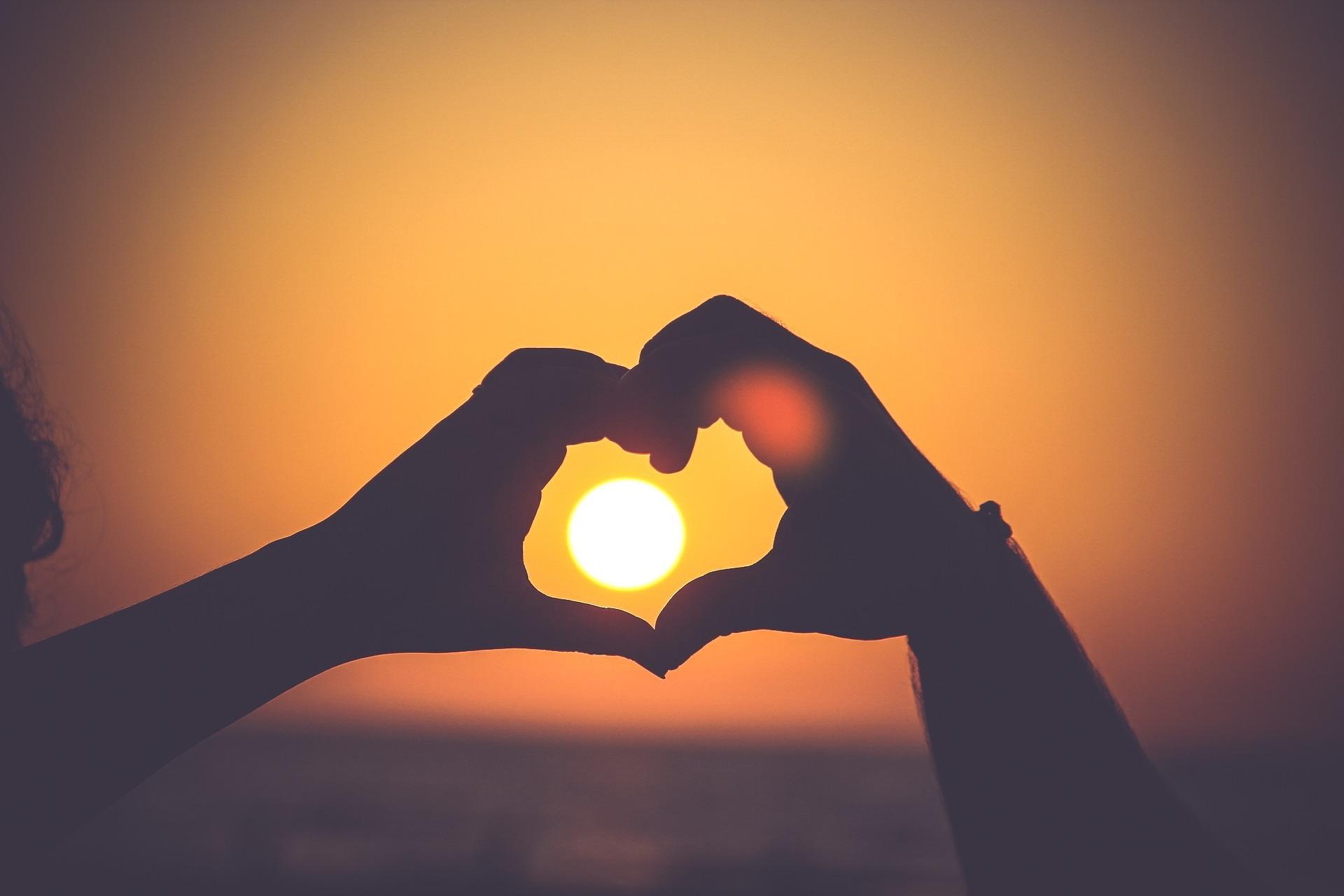 Sole al tramonto tra due mani che formano un cuore