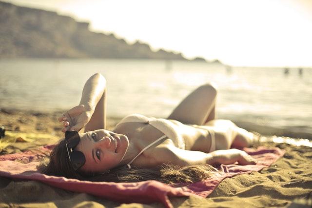 Ragazza che prende il sole sulla spiaggia